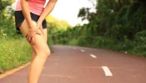 Übersäuerte Sportlerin hält sich den Oberschenkel