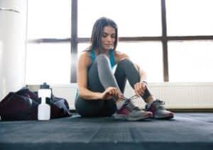 Übersäuerte Sportlerin mit Trinkflasche bindet sich die Schuhe