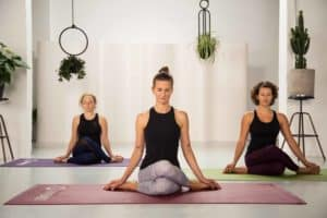 3 junge Frauen sitzen in hellem Raum auf bunten Yogamatten im Schneidersitz und geschlossenen Augen