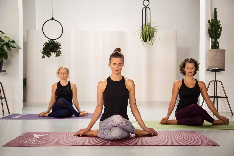 3 junge Frauen sitzen in hellem Raum auf bunten Yogamatten im Schneidersitz und geschlossenen Augen machen Yin Yoga