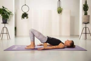 Junge Frau in Rückenlage mit angehobener Hüfte in hellem Raum auf lila Yogamatte mit geschlossenen Augen