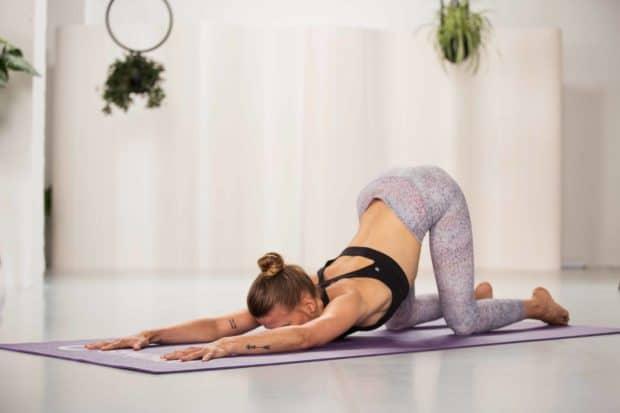 Junge Frau kniet in hellem Raum auf lila Yogamatte mit nach vorne gestreckten Armen - Child Pose aus dem Yin Yoga