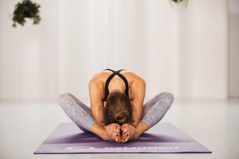 Junge Frau sitzt in hellem Raum auf lila Yogamatte im Schneidersitz und lehnt sich nach vorne