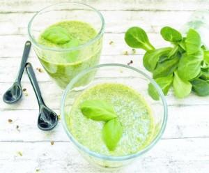Grüner Smoothie im Glas, dekoriert mit Basilikumblättern