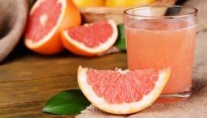 Eine Scheibe Grapefruit neben einem Glas frisch gepresstem Grapefruitsaft