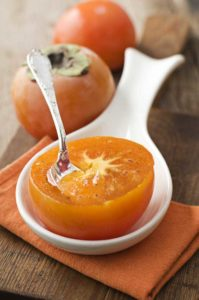 Halbierte orangefarbige Kaki mit Löffel