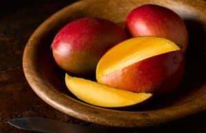 Eine in Scheiben geschnittene Mango, dahinter zwei ganze, rote Mangos