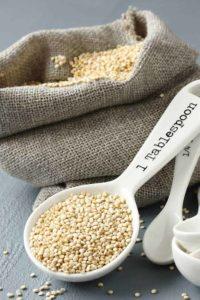 Quinoa-Körner auf Holzlöffel und in einem Jutesack