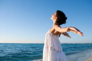 Frau mit geweiteten Armen steht am Strand