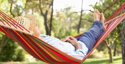 Mann liegt in Hängematte in einem Park