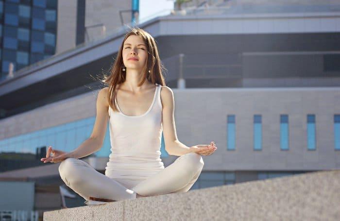 Frau sitzt im Schneidersitz auf einer Mauer