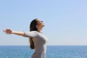 Frau steht mit offenen Armen am Meer