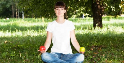 Frau in Jeans und weißem Tshirt sitz im Schneidersitz auf grünem Rasen mit einem roten Apfel in der rechten und einem grünen Apfel in der anderen Hand.