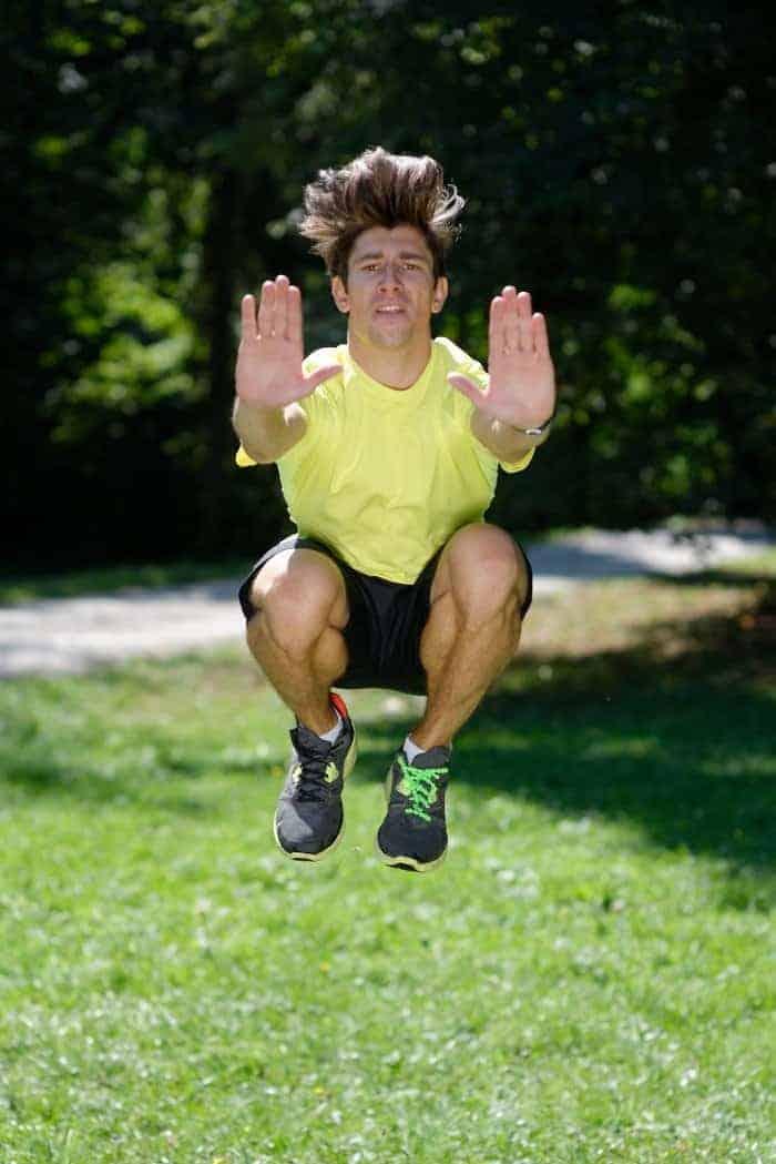 Mann macht Tuck Jumps im Park