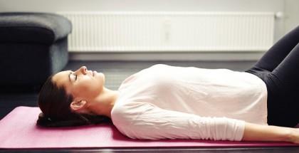 Frau liegt mit Yogamatte im Wohnzimmer