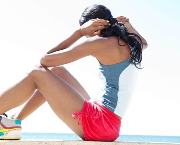 Junge Frau mit dunklen Haaren sitzt aufrecht mit gedrehtem Oberkörper und macht Bauchtraining