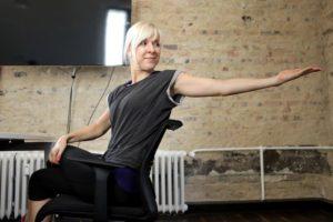 Blonde Frau sitzt auf Bürostuhl streckt einen Arm nach hinten aus und dreht sich um.