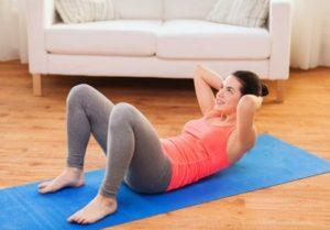 Frau im Wohnzimmer auf blauer Yogamatte mit weißer Couch im Hintergrund macht Crunches