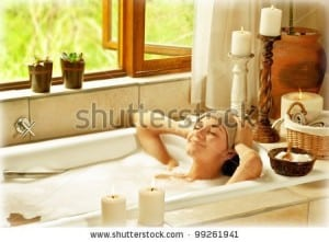 Junge Frau entspannt und glücklich mit geschlossenen Augen in der Badewanne mit Schaum und Kerzen