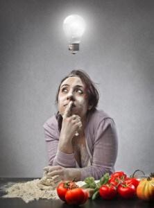 Frau sitzt an Tisch mit Gemüse und Mehl drauf. Über dem Kopf leuchtet eine Glühbirne