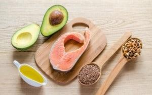 Avocado, Lachs, Samen und Öl auf einem Tisch mit Holzbrett und Holzlöffel