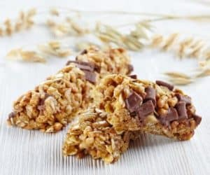 Schoko-Müsliriegel auf Holztisch mit Getreide