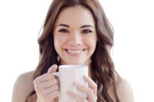 Junge dunkelhaarige Frau lacht und trinkt Kaffee au einer weißen Tasse