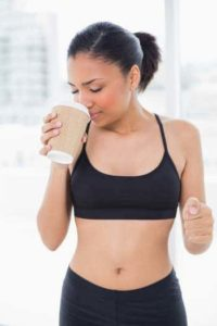 Dunkelhaarige Frau im Sportdress mit Kaffeebecher in der rechten Hand