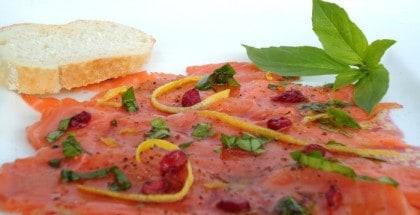Lachscarpaccio mit Granatapfelkernen, Zesten einer Zitrusfrucht und Basilikum