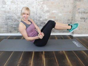 Frau mit blonden Haaren trainiert auf einer Yogamatte von Gymondo