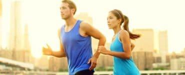 Junger Mann und junge Frau mit blauen T-Shirts joggen nebeneinander mit optimalem Trainingspuls