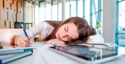 NAchmittagstief: Junge Frau im Büro liegt mit dem Kopf auf dem Schreibtisch und schläft