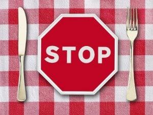 Stopschild mit Messer und Gabel auf rot weiß karieter Tischdecke