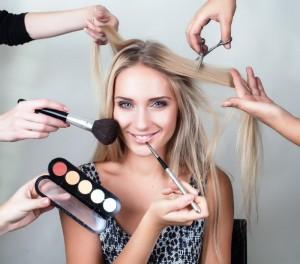 Viele Hände schminken eine Frau mit blonden Haaren