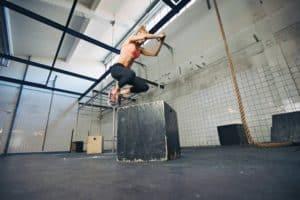 Junge, blonde, trainierte Frau mit rosa Sport Top und schwarzer leggins springt auf eine schwarze Kiste