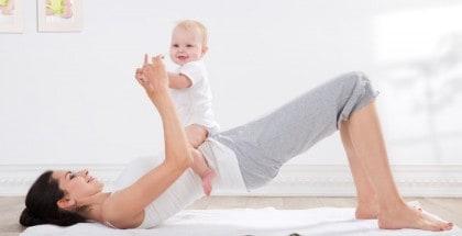 Junge Frau mit dunklen Haaren und weißem T Shirt liegt auf dem Rücken auf einem weißen Handtuch und hebt die Hüfte an. Ein lachendes Baby sitzt auf ihrem Schoß.