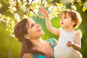Mutter mit Kind bei Sonne unter einem Kirschbaum