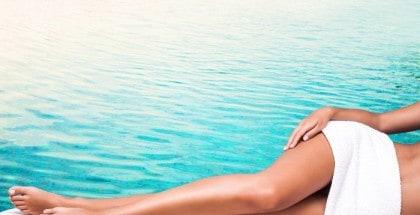 Frau liegt seitlich vor einem Hintergrund mit türkisenem Wasser und streckt ihre schlanken, leicht gebräunte Beine seitlich aus.
