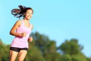 Junge Frau mit braunen Haaren und rosa Trägershirt lacht beim Jogging durch die Natur