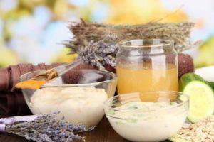 Drei Glasschalen mit unterschiedlichen Peelings gefüllt auf einem Holztisch mit Kräutern und Quark und Honig