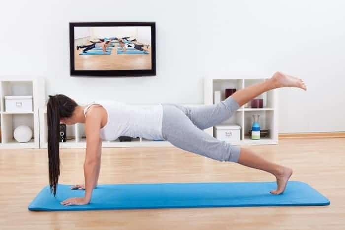 Junge Frau mit schwarzen, langen Haaren trainiert zu Hause auf einer blauen Trainingsmatte. Sie hat die Hände aufgestützt, ein Bein angehoben und blickt auf einen Bildschirm, auf dem Leute zu sehen sind die trainieren.