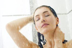 Gesicht einer jungen Frau mit geschlossenen Augen unter der Dusche.