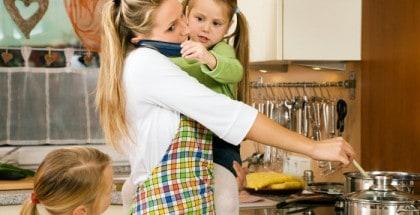 Mutter mit Kind auf dem Arm kocht in der Küche. Zweite Tochter steht neben Ihr. Kind auf dem Arm der Mutter hält der Mutter ein Telefon ans Ohr.