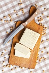 In Stücke geschnittener Tofu auf einem hölzernen Schneidebrett neben einem Messer umgeben von reifen Sojabohnen