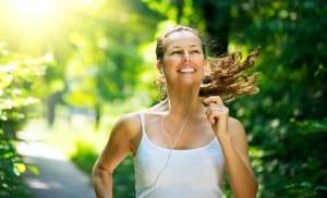 Junge Frau mit weißem Trägertop joggt durch den Wald, lacht und hört Musik.