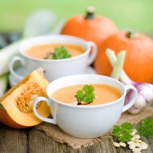 Kürbissuppe in weißer Suppentasse serviert, arrangiert neben Kürbissen und Zwiebeln