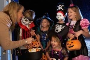Frau verschenkt an in Halloweenkostümen verkleideten Kindern gesunde Süßigkeiten
