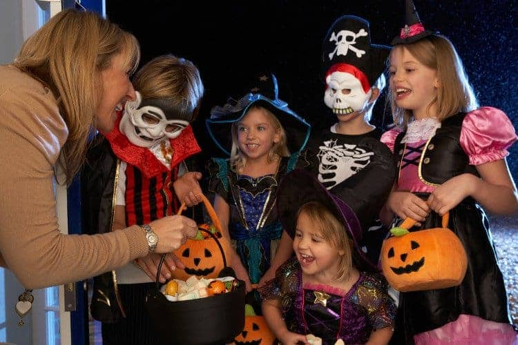 Frau verschenkt an in Halloweenkostümen verkleideten Kindern gesunde Süßigkeiten, Halloween Rezepte