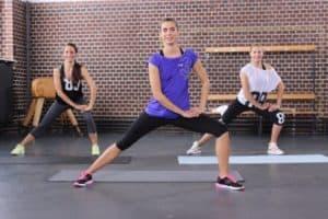 Drei Trainerinen mit bunter Kleidung machen seitliche Ausfallschritte bzw. Side Lunges