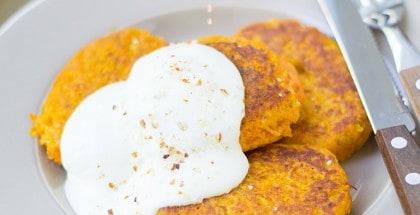 Drei Möhren-Couscous-Bratlinge mit Quark auf weißem Teller serviert